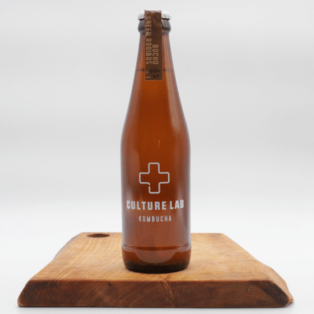 Buchu & Green Rooibos kombucha bottle on a wooden board with a white background