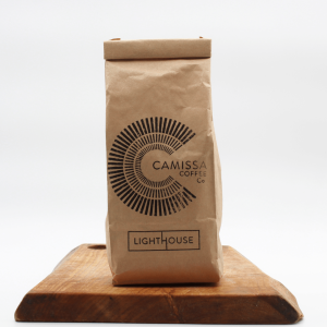 Camissa lighthouse coffee sitting on a wooden board with a white background