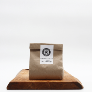 Mung Beans in biodegradable packaging sitting on a wooden board with a white background.