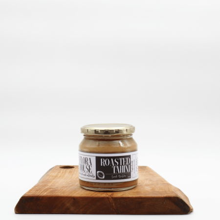 Flora House Tahini Butter sitting on a wooden board with a white backgroind
