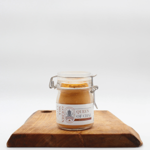 Golden Latte in a glass jar on a wooden board with a white background