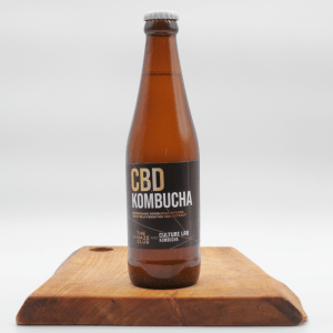 Kombucha CBD bottle on a wooden board with a white background