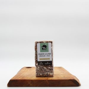Cranberry & Almond Stack with mixed seeds, dark chocolate and coconut flakes on a wooden board with a white background.