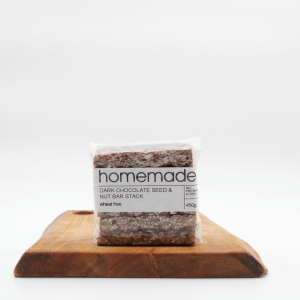 Homemade Dark choc nut seed bar sitting on a wooden board with a white background