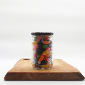 Jelly beans in a jar sitting on a wooden board with a white background.