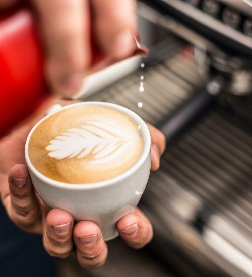 barista-pouring-milk-into-art-cappuccino-PZBDNRX
